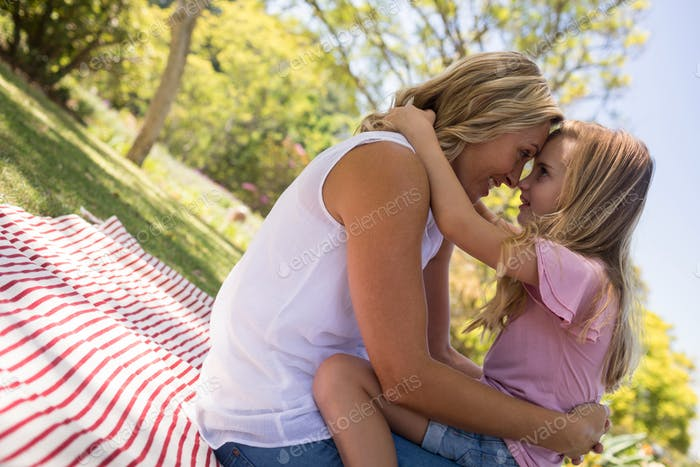 Happy mother embracing her daughter in park