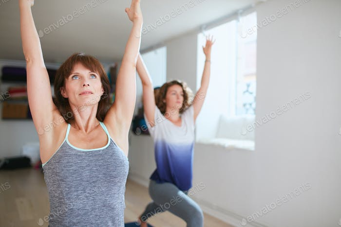 Two women practicing yoga forms at class