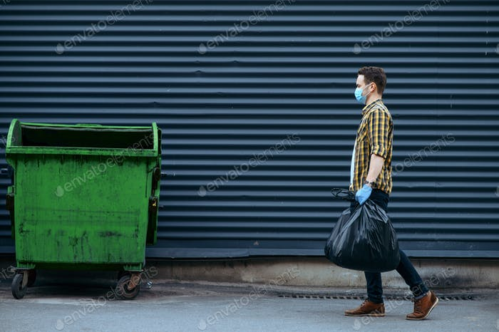 Volunteer carries plastic trash bags to the can