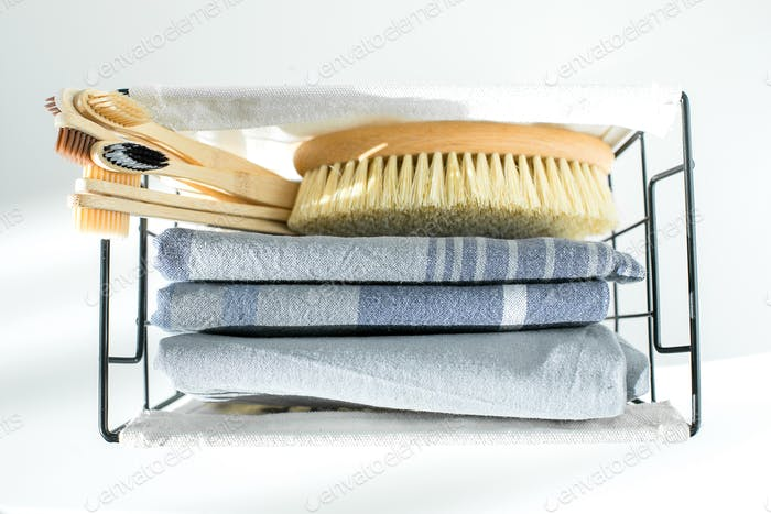 Eco natural body brush, wooden bamboo toothbrush and cotton face towels in metal basket. Zero waste