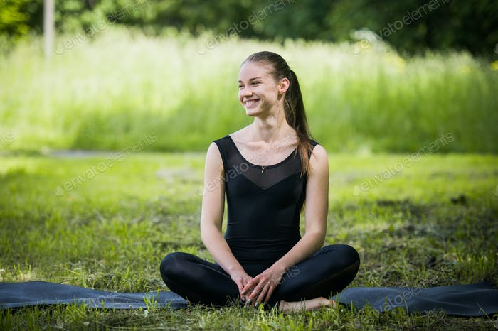 Portrait of sporty woman doing stretching exercises in park before training. Female athlete