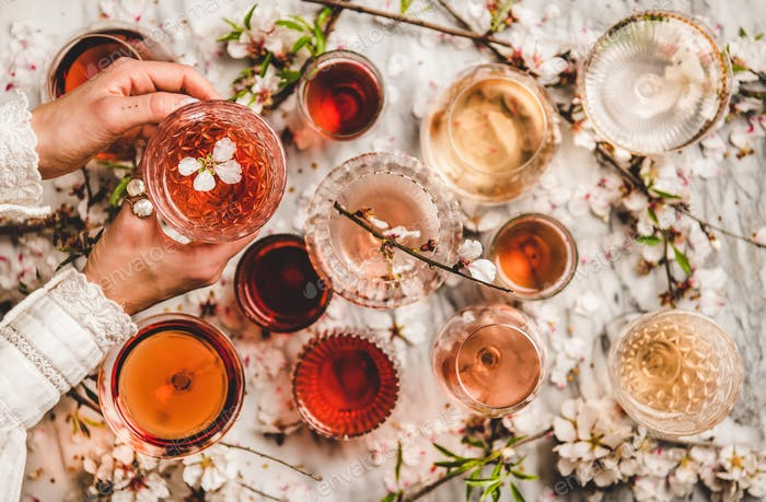 Womans hands over shades of rose wine over marble background