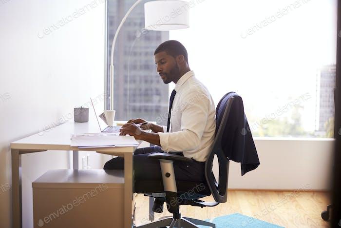 Businessman Sitting At Desk Working On Laptop In Modern Office