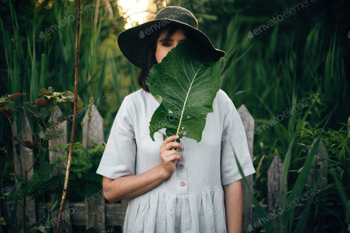 Stylish girl in linen dress holding big green leaf at face