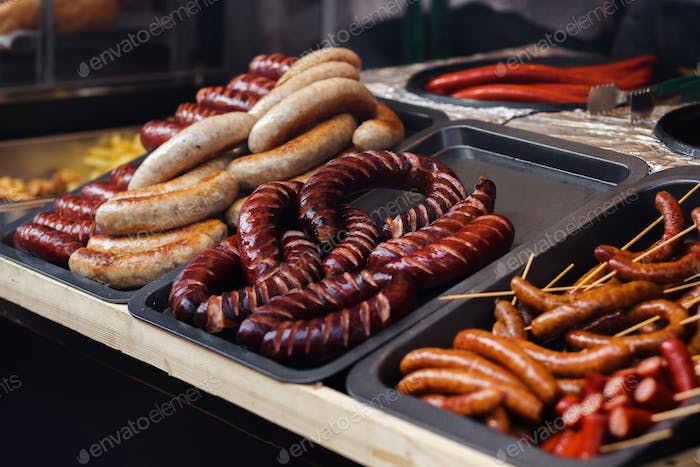 Delicious sausages bbq at market fest, grilling on open grill, outdoor kitchen
