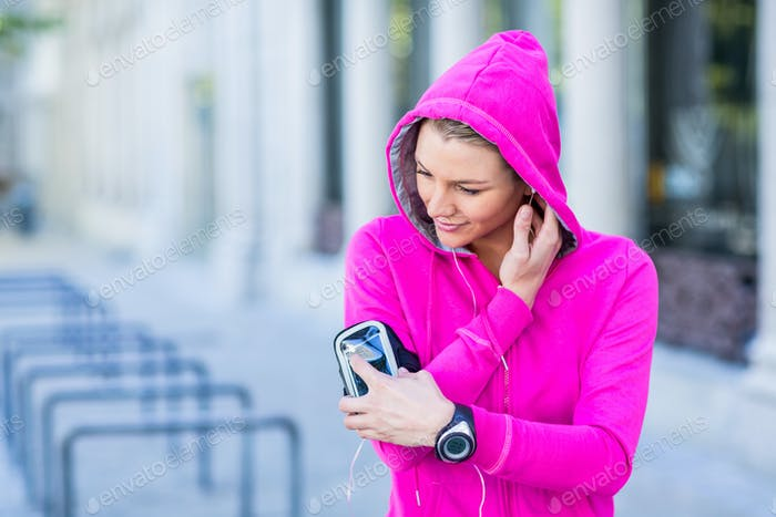 A woman wearing a pink jacket using her phone on a sunny day