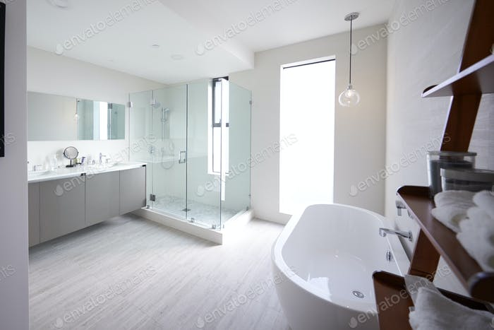 Modern domestic bathroom with shower cabin and freestanding bath, sunlight, no people