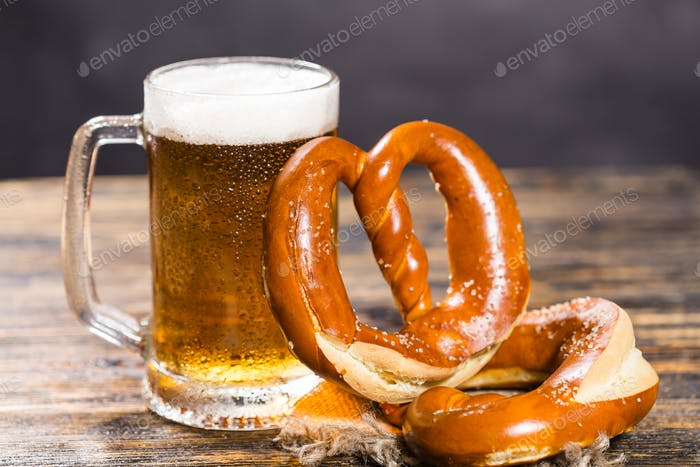 Food and drink concept - beer mug with german pretzel