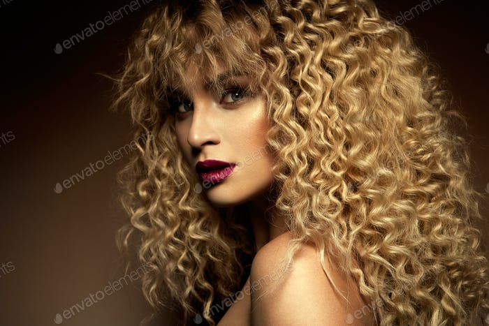 Beautiful face of a fashion model with blue eyes.Curly hair. Red lips.