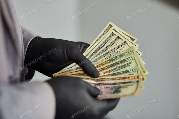 Mann hält Geld Dollar in der Hand in schwarzen medizinischen Handschuhen.