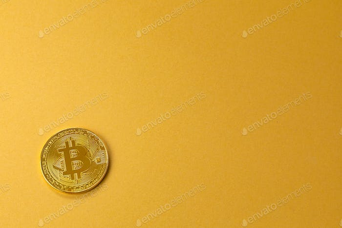 Gold bitcoin crypto currency coin on gold yellow backgound
