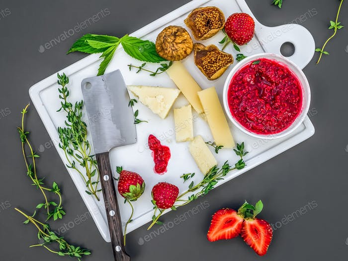 A set of cheese, fresh strawberries, herbs, dried figs and raspb