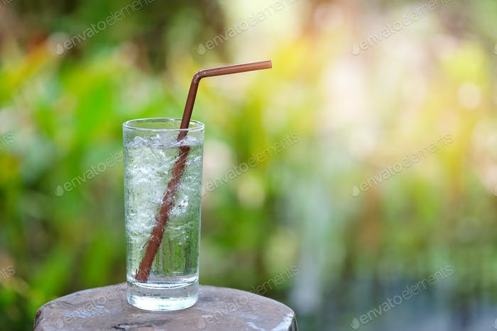 Glass water on wooden table with green blurred background.