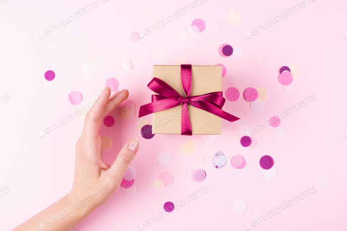 Woman`s Hand and Gift Box on Pink Background.