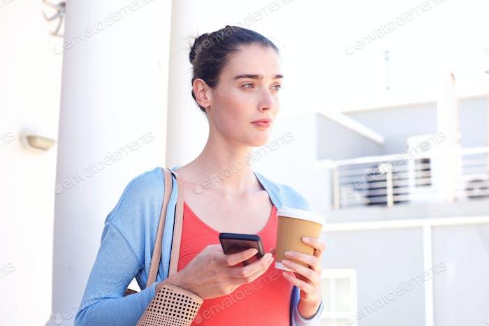 Attraktive Frau im Inneren hält Kaffee und Handy