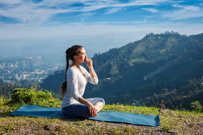 Woman practices pranayama in lotus pose outdoors