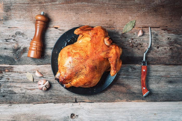 Whole roasted chicken on plate, pepper shaker, meat fork, garlic, spices over wooden background. Top
