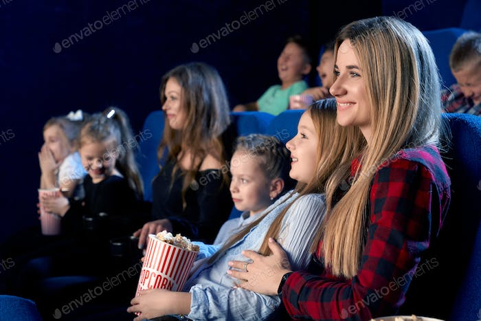 Mother holding daughter on knees in cinema