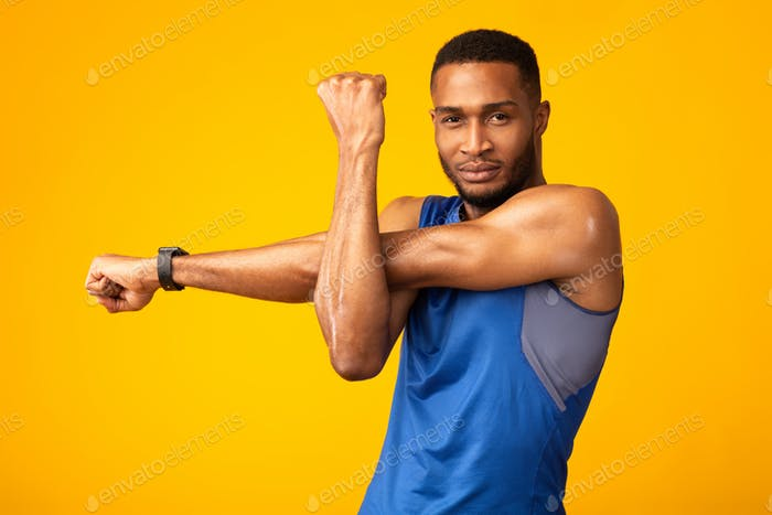 Healthy black guy stretching hand and shoulder before workout