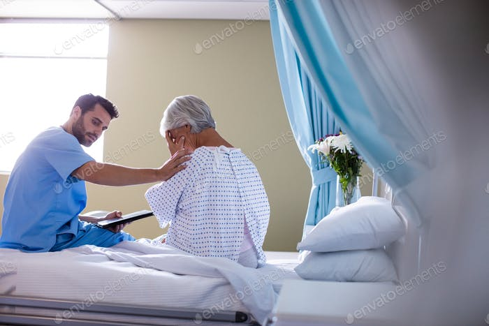 Male doctor consoling a senior patient on bed