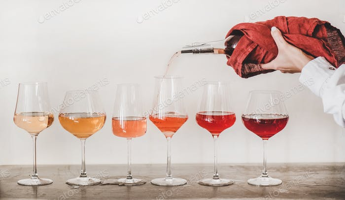 Rose wine glasses and womans hand pouring wine, white background