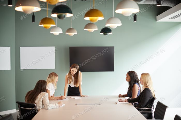 Group Of Businesswomen Sitting Around Boardroom Table And Collaborating On Task