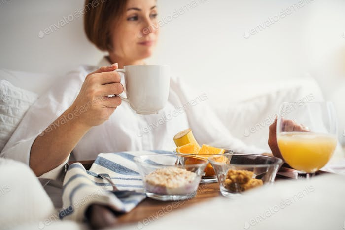 A woman with breakfast in bed in the morning, using smartphone.