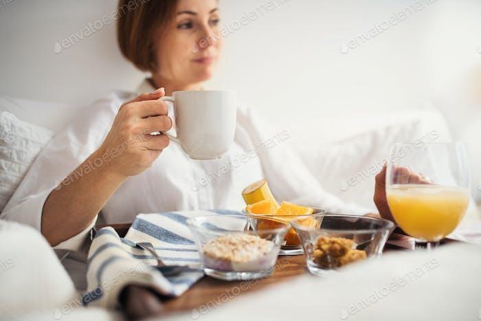 Eine Frau mit Frühstück im Bett am Morgen, mit Smartphone.