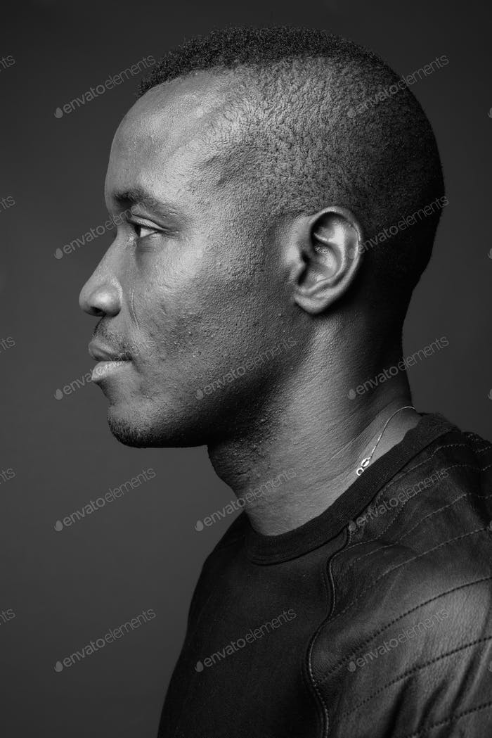 Studio shot of young African man against gray background