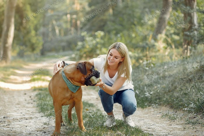Girl in a summer forest playing with dog