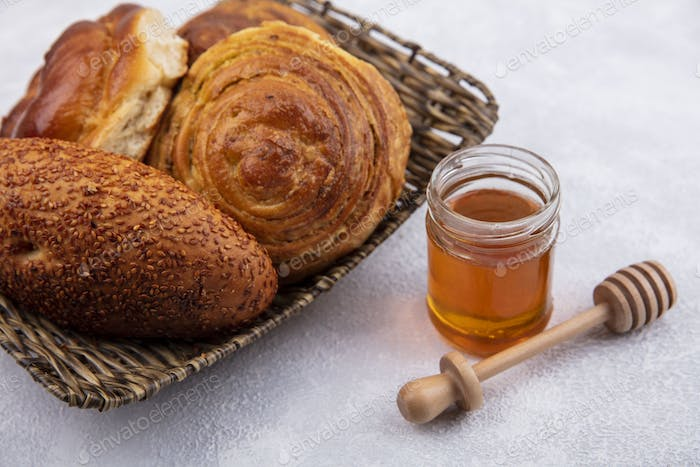 top view of buns on a bucket with honey on a glass jar and wooden honey spoon on a white background