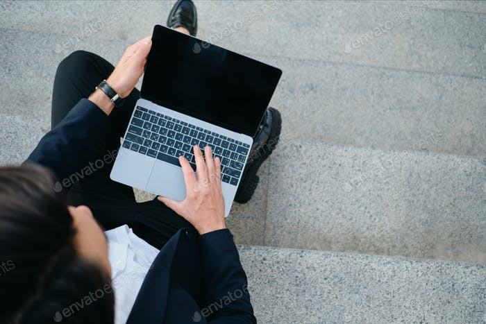 Close up man in classic suit sitting on stairs outdoor working on modern laptop alone