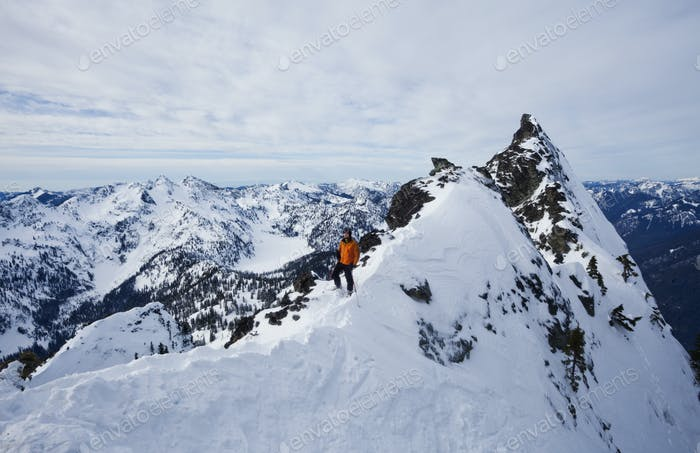 A skier on a ridgeline,pausing before skiing down a slope