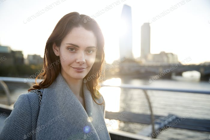 Young white woman wearing grey coat standing on Millennium Bridge, London, looking to camera smiling