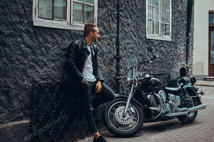 Fashionable biker dressed in a black leather jacket leaning on a wall near his retro motorcycle