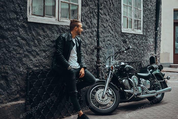 Modische Biker gekleidet in einer schwarzen Lederjacke lehnt sich an eine Wand in der Nähe seines Retro-Motorrad