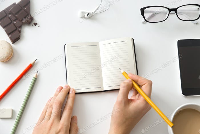 Student female hands holding a pencil and open notebook