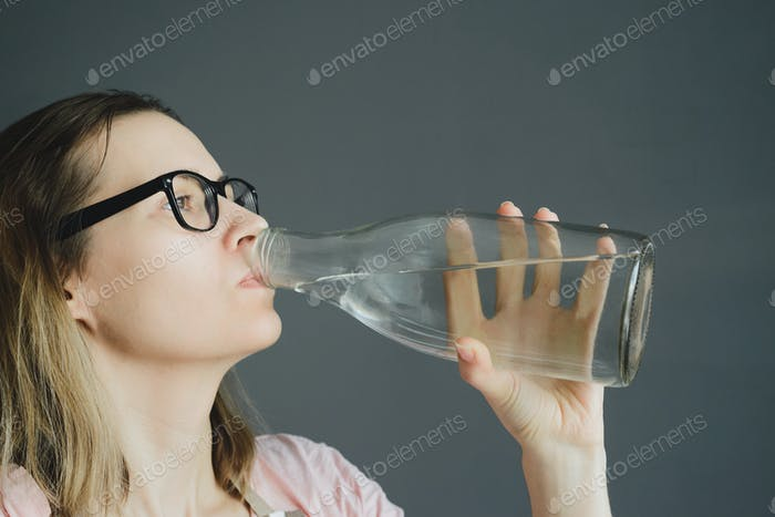 woman in glasses drinks water from glass bottle