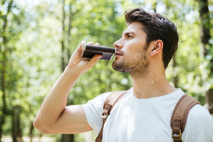 Man with backpack standing and drinking from flask in forest