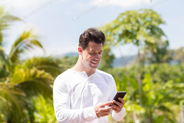 Handsome Mann Messaging mit Handy Smartphone über Tropical Forest und Blue Sky Young Guy Chat