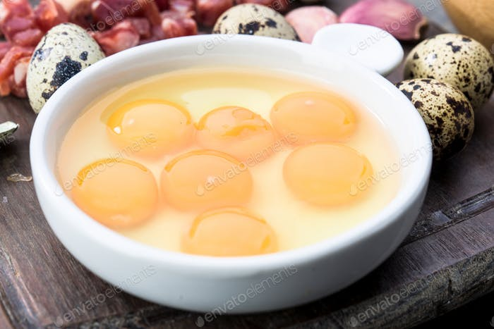 raw and open quail eggs in porcelain bowl, on rustic wood