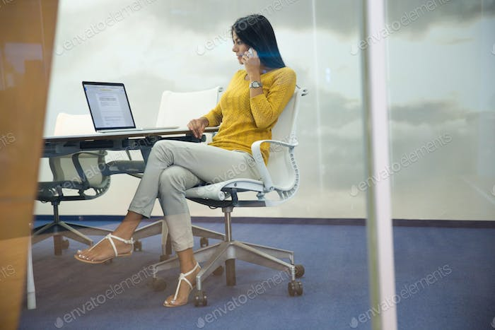 Businesswoman talking on the phone at her workplace in office