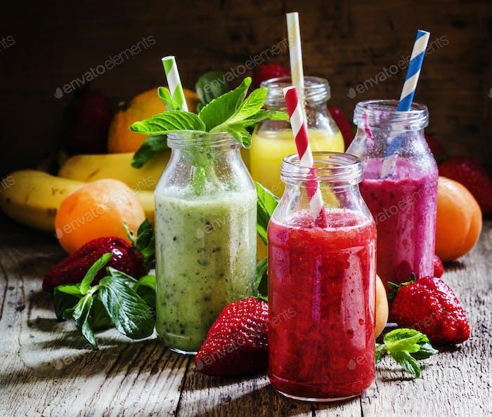 Fruchtsmoothies mit farbigen Strohhalmen in Glasflaschen