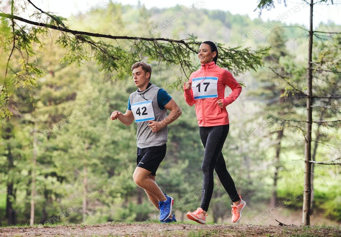 Young couple running a race competition in nature.