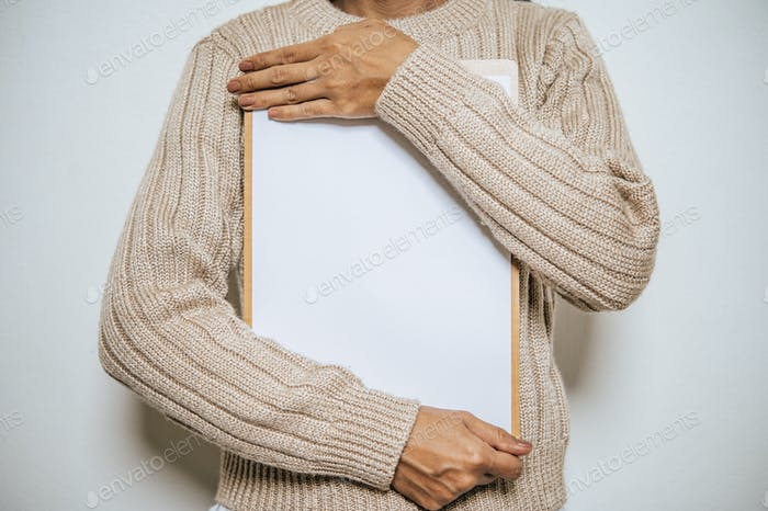 A people with long sleeves holds a clipboard on his chest.