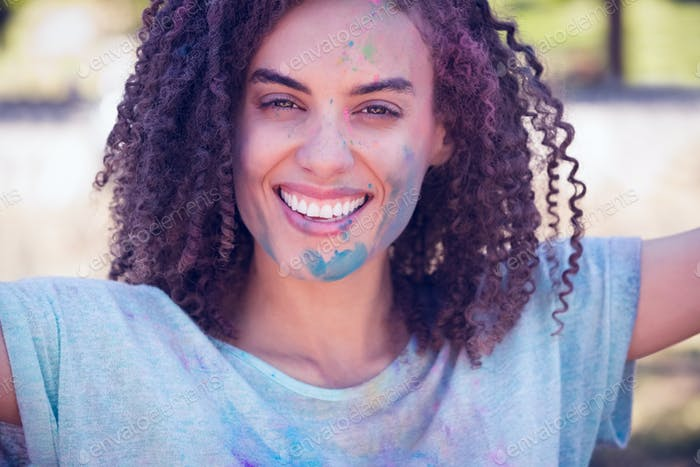 Pretty brunette covered with powder paint on a sunny day