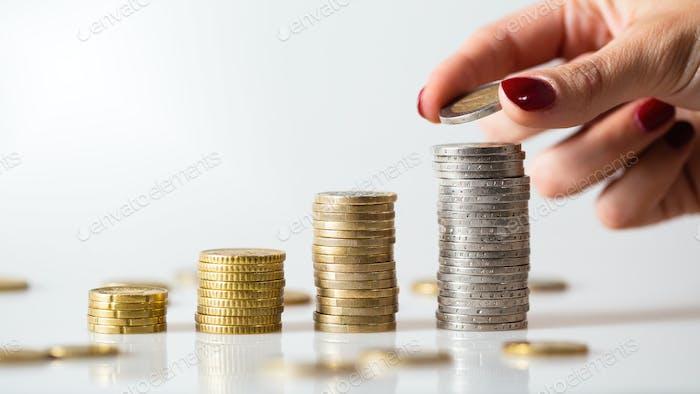 Ahorro de dinero en montones de monedas sobre fondo blanco