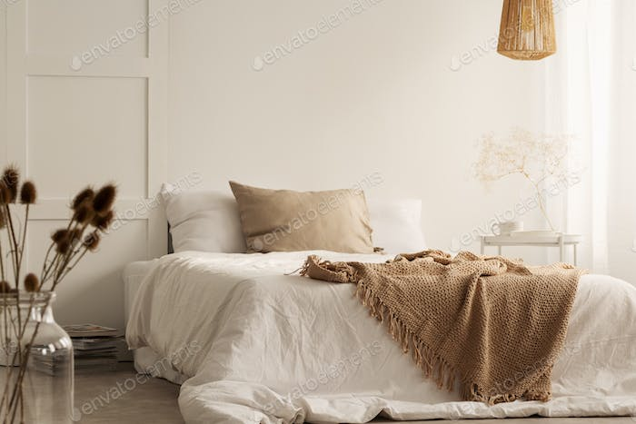 Flowers and lamp in white natural bedroom interior with blanket