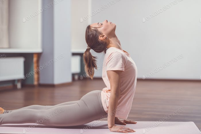 Young girl practicing yoga in class