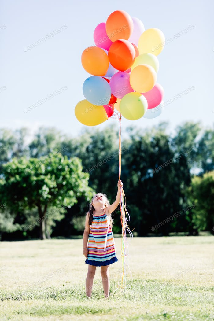 Happy little girl looking upon the bunch of balooons